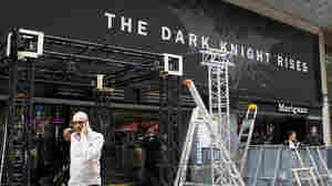 Workers dismantle an installation that was set up for the premiere of The Dark Knight Rises in Paris. It had been scheduled for Friday night but was canceled after a gunman killed 12 people at a Colorado opening of the same film.