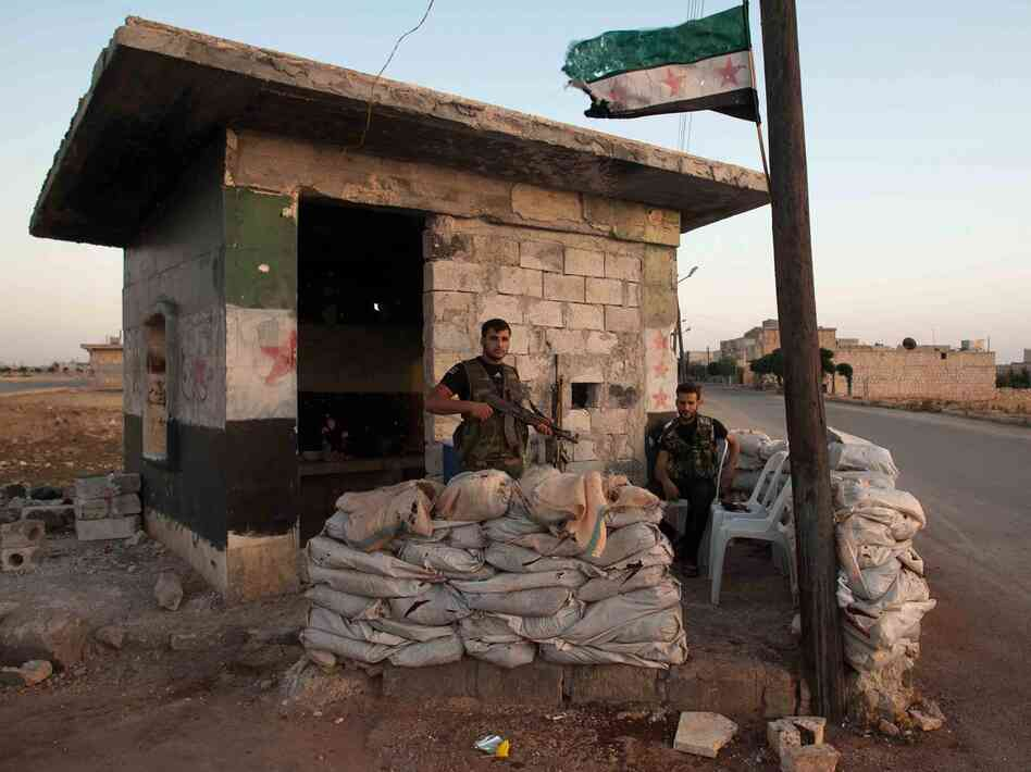 Members of the Free Syria Army stand guard at an outpost on the outskirt of Mareh, near Aleppo in northern Syria, on June 27.