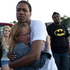 Judy Goos hugs Isaiah Bow, in front of her daughter, Emma Goos, and Terrell Wallin outside Gateway High School in Denver, Colo., on Saturday. Emma Goos and  Wallin witnessed the shooting.
