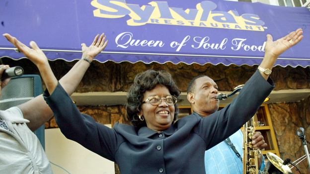 Sylvia Woods moves to the music outside her restaurant in Harlem neighborhood of New York, during the restaurant's 40th anniversary celebration in 2002. (AP)