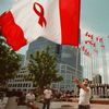 Kim Gerlach of Vancouver waves the flag designed by Affirmative Aids Action for the XI International Conference on AIDS, July 1996.