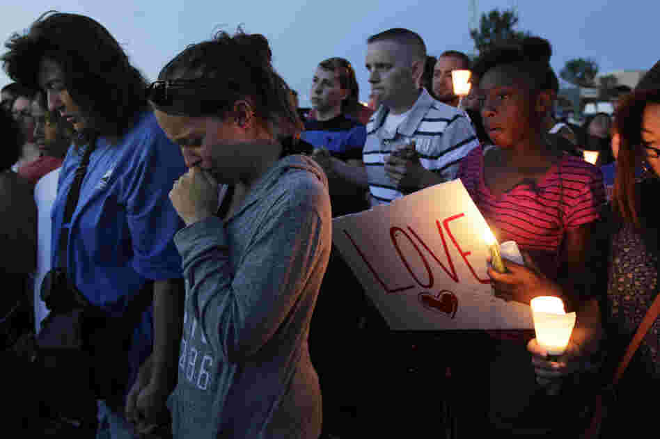 Crowds gathered to honor the victims of the attack Friday in Aurora. Witnesses said the shooter came into the theater dressed in black after the film had already started.