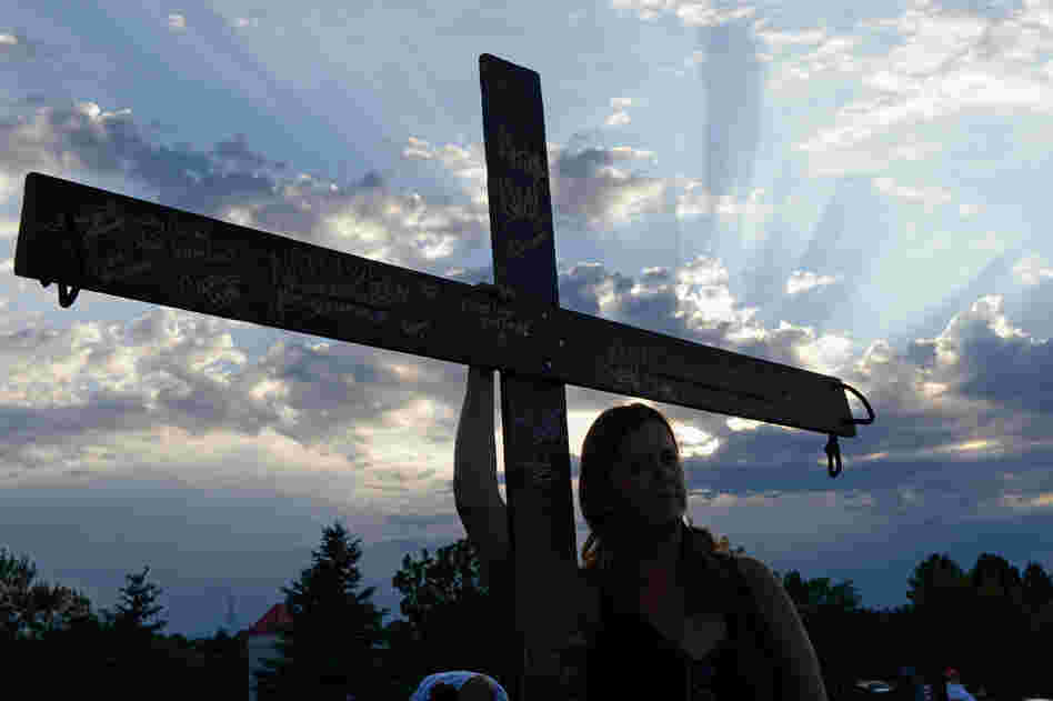 A woman holds a cross for the victims at the movie theatre Friday.