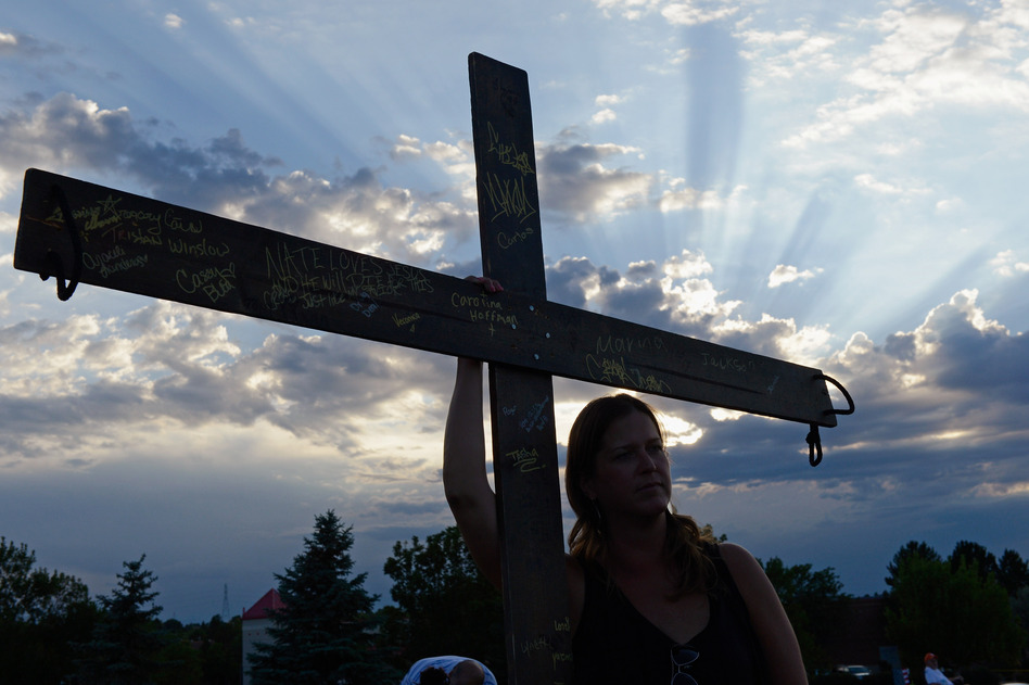 A woman holds a cross for the victims at the movie theatre Friday. (Getty Images)