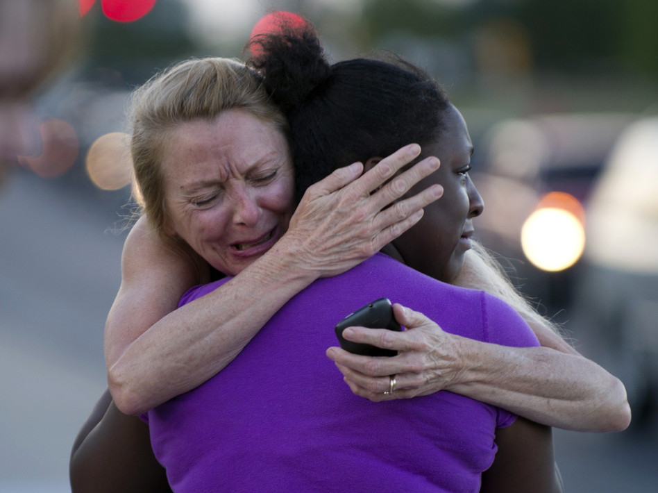 Two women mourn near the Century 16 theater in Aurora, Colo., where a gunman opened fire during the opening of the new Batman movie, The Dark Knight Rises. (AFP/Getty Images)
