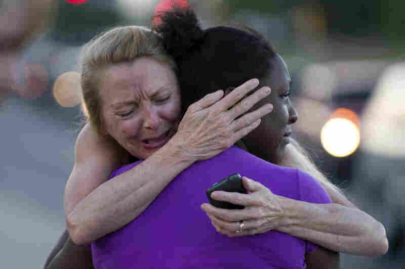 Two women mourn near the Century 16 theater Friday.