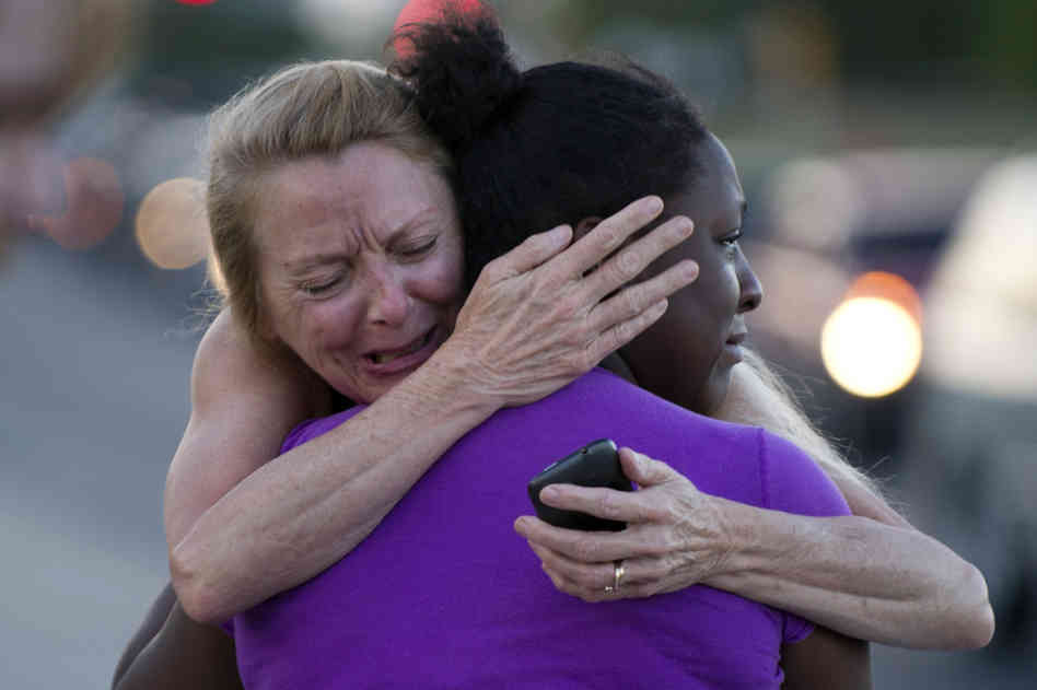 Two women mourn near the Century 16 theater in Aurora, Colo., where a gunman opened fire during the opening of the new Batman movie, The Dark Knight Rises.