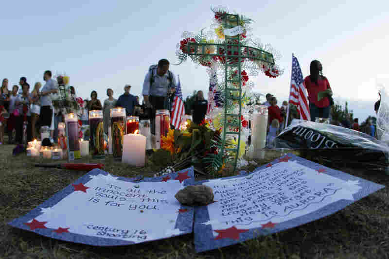 "A written message that begins ""To all the innocent souls ... this is for you,"" is shown near other tributes Friday in Aurora."