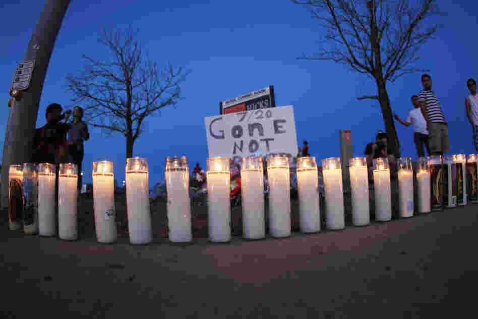 As night falls Friday, candles sit iluminated along the sidewalk in front of a makeshift memorial for the victims. After the shooting, 24-year-old suspect James Holmes was arrested.