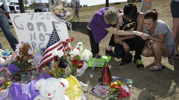 Pastor Mary Lu Saddoris (left) prays with Isaac Pacheo (center) and Courtney McGregor near a photo of their friend Alex Sullivan on Saturday at a memorial near the movie theater in Aurora, Colo. (AP)