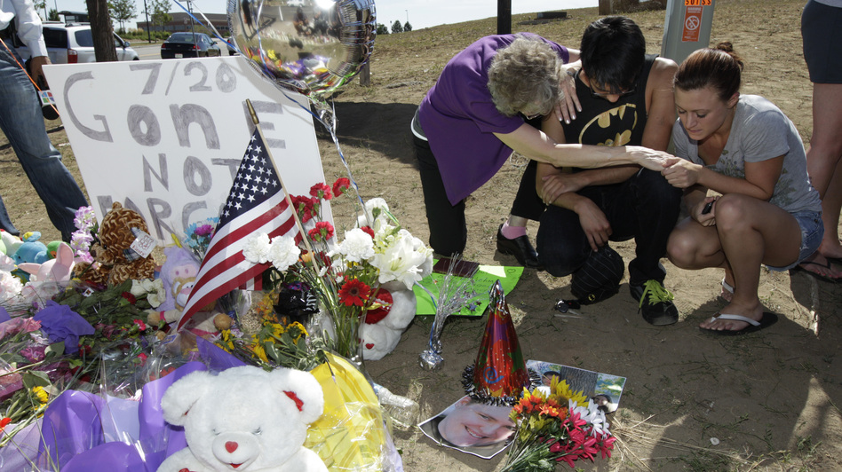 Pastor Mary Lu Saddoris (left) prays with Isaac Pacheo (center) and Courtney McGregor near a photo of their friend Alex Sullivan on Saturday at a memorial near the movie theater in Aurora, Colo.