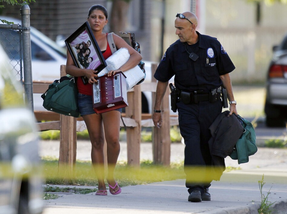 An Aurora police officer assists a woman carrying her belongings from her home near the apartment of alleged gunman James Holmes. Bomb technicians are working to defuse his booby-trapped apartment.