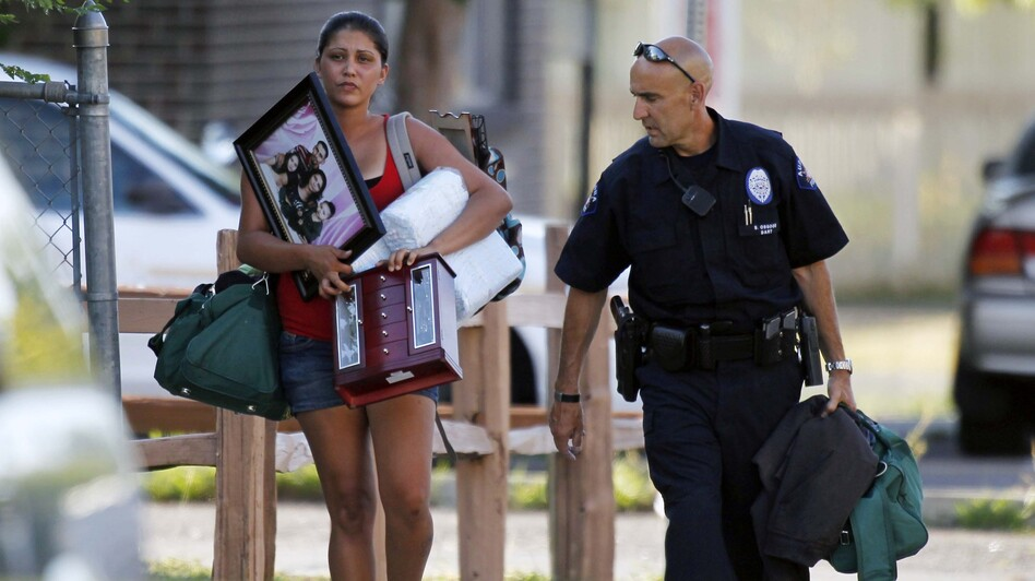 An Aurora police officer assists a woman carrying her belongings from her home near the apartment of alleged gunman James Holmes. Bomb technicians are working to defuse his booby-trapped apartment. (AP)