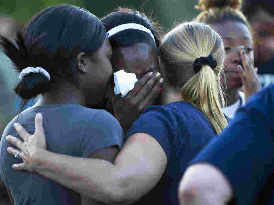 Mourners at a vigil Friday near the theater in Aurora, Colo., where 12 people were killed and about 58 wounded.