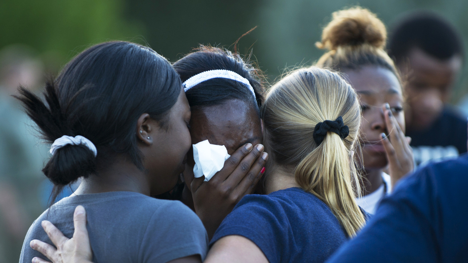 Mourners at a vigil Friday near the theater in Aurora, Colo., where 12 people were killed and about 58 wounded. (AFP/Getty Images)