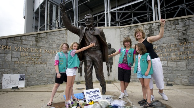 A Pennsylvania Girl Scout Troop poses with the statue of former Penn State University football coach Joe Paterno outside Beaver Stadium in State College, Pa., on Saturday. (Getty Images)