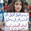 "In this image taken July 16 and provided by Edlib News Network, a Syrian girl holds a poster that reads, ""Greetings from Kfarnebel's children to the Free Syrian Army soldiers in Damascus,"" during a demonstration in Kfarnebel, Syria. Rebels hold large swaths of territory in rural Syria. Fighters in the village of Atima recently launched their first operation against the regime."