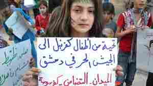 """In this image taken July 16 and provided by Edlib News Network, a Syrian girl holds a poster that reads, """"Greetings from Kfarnebel's children to the Free Syrian Army soldiers in Damascus,"""" during a demonstration in Kfarnebel, Syria. Rebels hold large swaths of territory in rural Syria. Fighters in the village of Atima recently launched their first operation against the regime."""