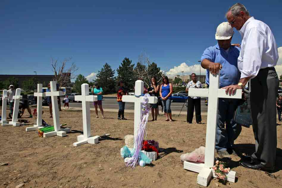 Aurora, Colo., Mayor Steve Hogan (right) says a prayer with Greg Zanis, from Aurora, Ill., as Zanis places crosses for the victims across the street from the movie theater where the mass shooting took place.