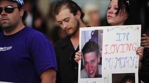 A sign is held in honor of Jonathan Blunk at a vigil in Aurora on Sunday. Blunk was one of the 12 killed in Friday's shooting.