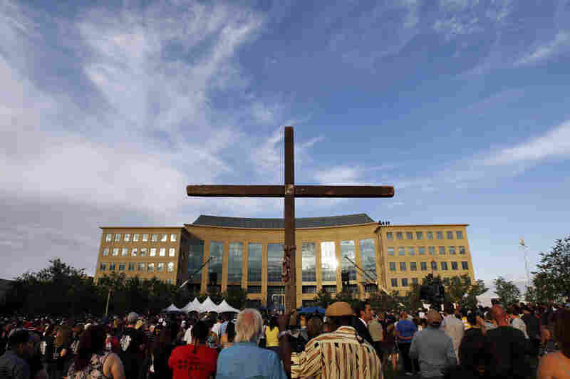 A cross stands among people gathered for the vigil at the Aurora Municipal Center Sunday.