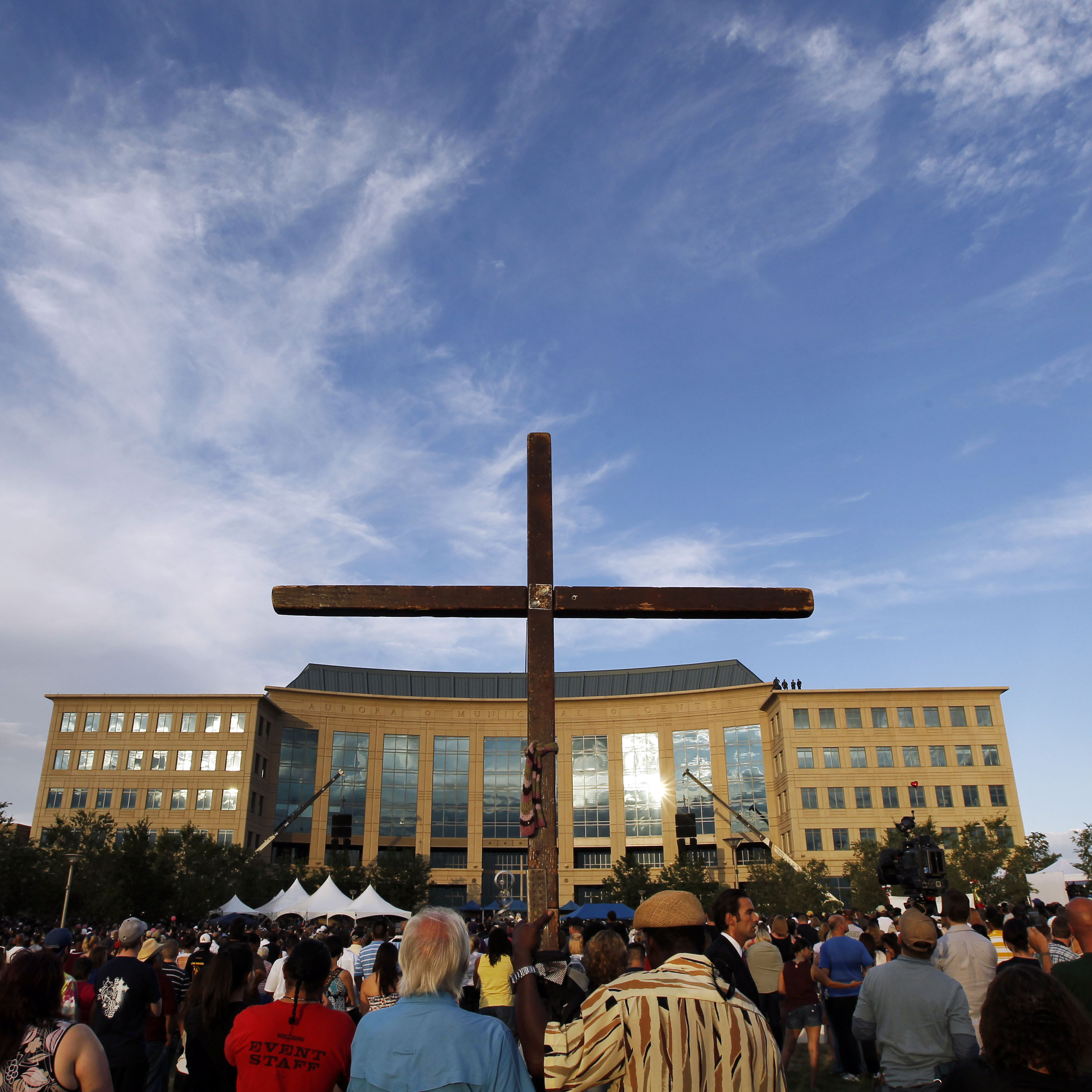 A cross stands among people gathered for the vigil at the Aurora Municipal Center in Aurora, Colo., on Sunday.
