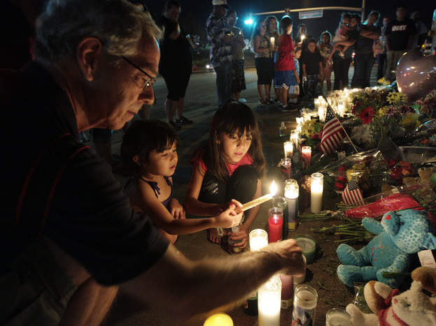 Ted Engelmann, left, helps Yamilet Ortega, 3, second from left, and Kimberly Hernandez, 7, light candles, Saturday at a memorial near the movie theater in Aurora, Colo., where a gunman killed 12 people and wounded dozens of others Friday. (AP)