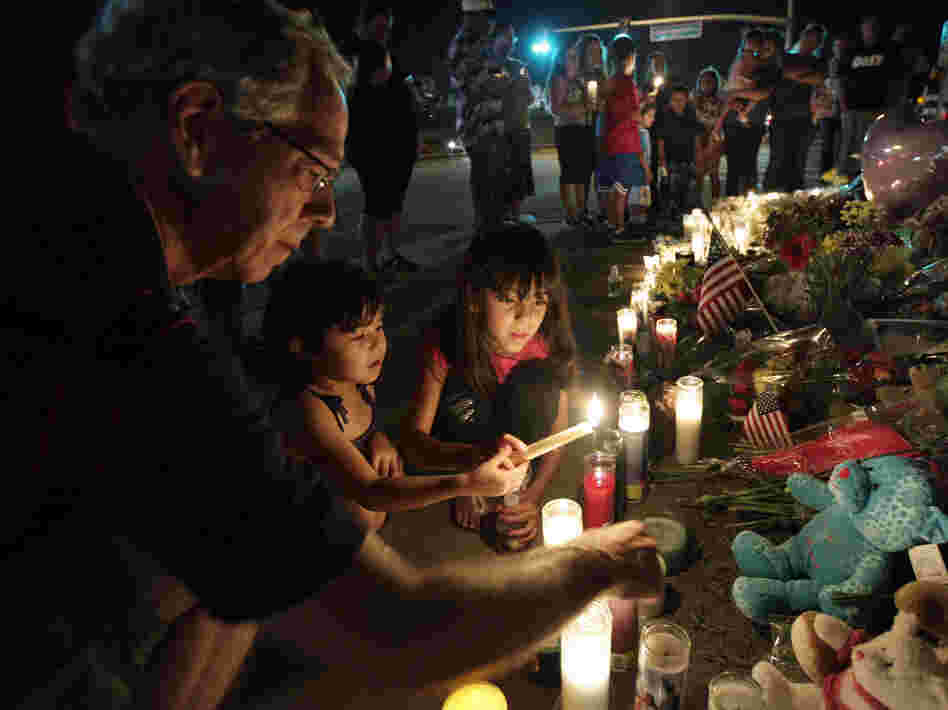 Ted Engelmann, left, helps Yamilet Ortega, 3, second from left, and Kimberly Hernandez, 7, light candles, Saturday at a memorial near the movie theater in Aurora, Colo., where a gunman killed 12 people and wounded dozens of others Friday.