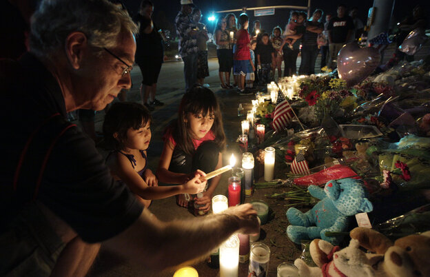 Ted Engelmann, left, helps Yamilet Ortega, 3, second from left, and Kimberly Hernandez, 7, light candles, Saturday, July 21, 2012, at a memorial near the movie theater in Aurora, Colo. where a gunman killed at least 12 people in one of the deadliest mass shootings in recent U.S. history.