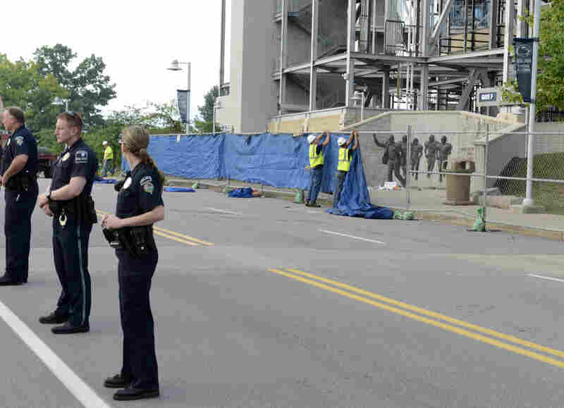 Police formed a line in front of Beaver Stadium as workers prepared to lifted the 7-foot-tall statue off its base and move it inside.