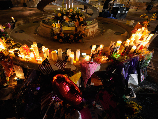 Mourners create a memorial at the fountain of the Aurora Municipal Center after a prayer vigil Sunday for the 12 victims of Friday's mass shooting at the Century 16 movie theater.