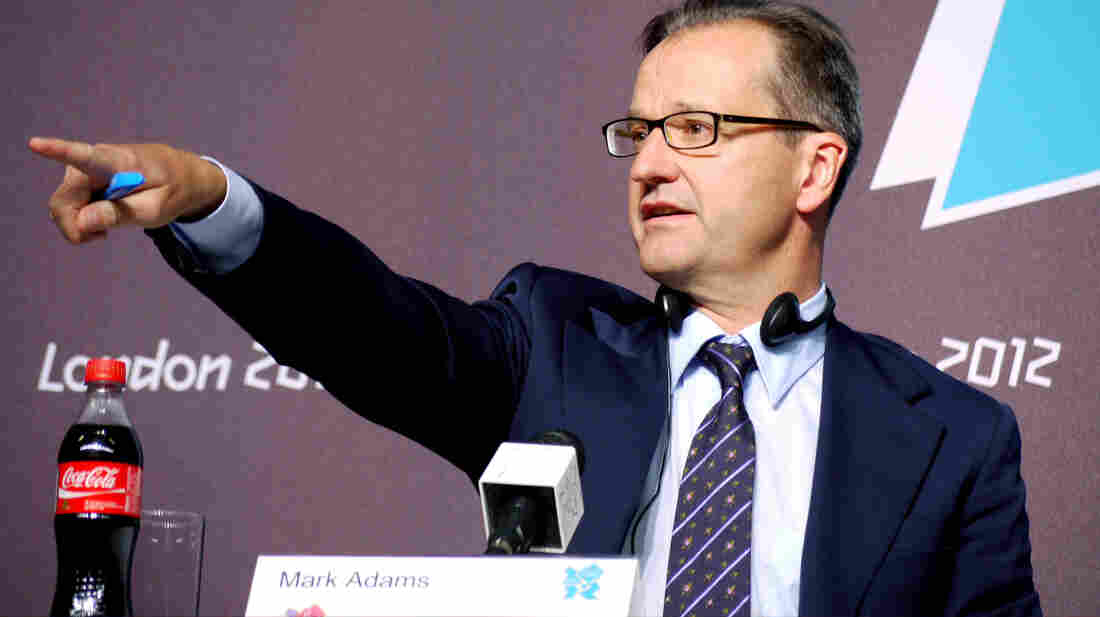 International Olympic Committee spokesman Mark Adams points to a reporter at a London news conference Saturday. The Olympic event may have been the first to have product placement.