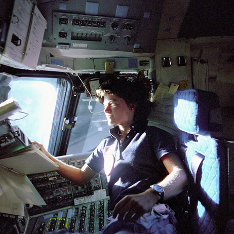 In this June 1983 photo provided by NASA, astronaut Sally Ride, a specialist on shuttle mission STS-7, monitors control panels from the pilot's chair on the shuttle Columbia flight deck.