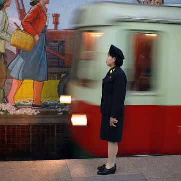 An attendant stands near the tracks as a metro train arrives in a subway station in Pyongyang, North Korea on August 20, 2007.