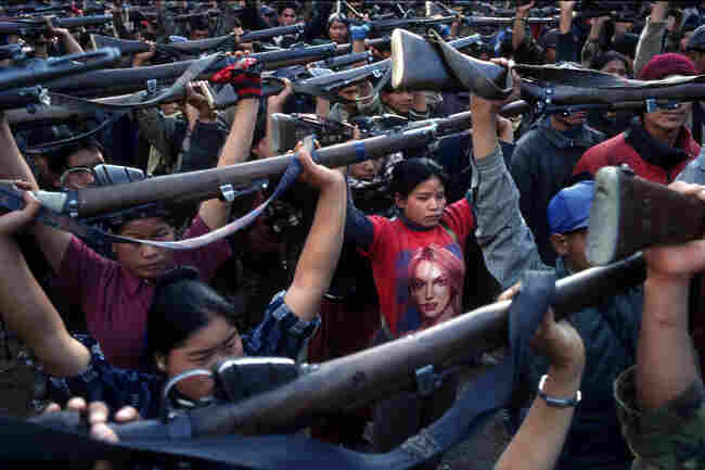 A Maoist rebel soldier in a Britney Spears T-shirt stands with soldiers of the People's Liberation Army during a drill in a schoolyard in the village of Gairigaon, Nepal, February 2005.