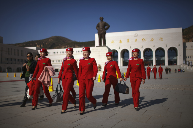 "An all-girls group of Young Communist League members walks past a statue of Chairman Mao Zedong in Yan'an, China, November 2009. Yan'an is promoted as the ""Revolutionary Holy Land"" and offers a number of museums, monuments and other ""Red Tourism"" sites supported by the Chinese government."