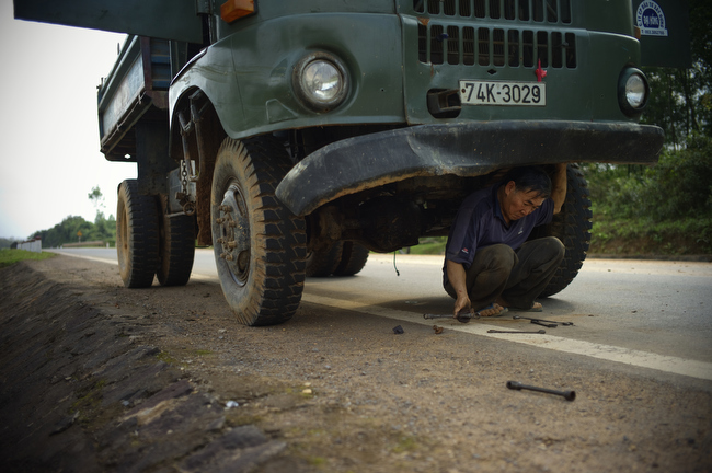 A truck driver repairs a broken Soviet truck along the Ho Chi Minh Highway inside the former demilitarized zone in Vietnam, February 2010.
