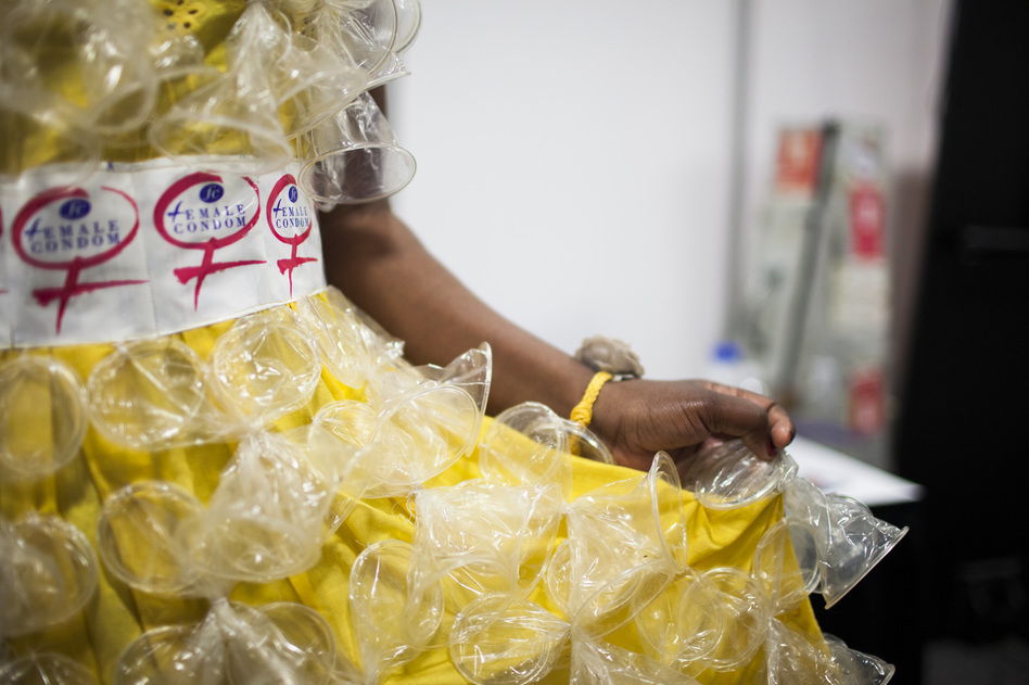"""Olwin Manyanye shows off her dress decorated with the latest type of female condom, called """"FC2."""" These second-generation condoms went on the market in 2009. They're more comfortable and increased the popularity and demand for this method of contraception method. (NPR)"""