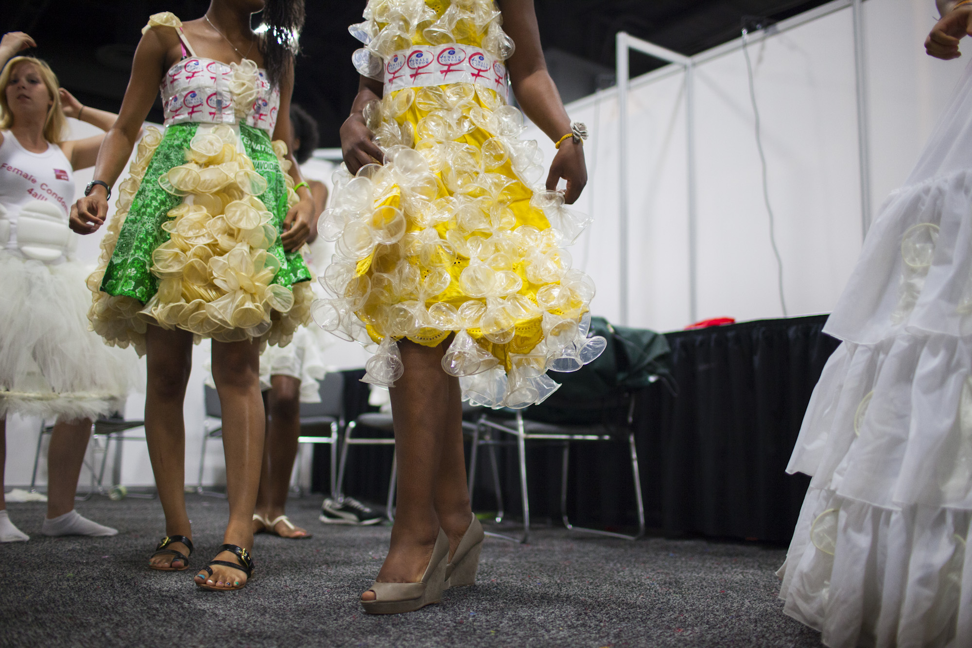 The show featured six dresses decorated with female condoms. Diamond Gillespie of Washington (left) and Olwin Manyanye of Zimbabwe rehearse backstage.