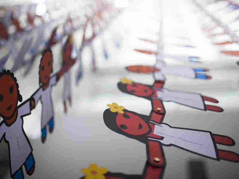 A paper doll chain with more than 25,000 cutouts hangs from the ceiling of the Washington, D.C. convention hall. Each doll displays a message about the power of female condoms to stop HIV.