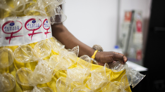 "At the International AIDS conference, a female condom fashion show raised awareness about the rising need for more female condoms. Olwin Manyanye of Zimbabwe shows off one of the dresses decorated with a second-generation female condom, called ""FC2."" (NPR)"