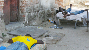 Men on cots wait for farm work near Calabria. Poor living conditions for migrant workers, sometimes without running water or toilet facilities, has led the Italian government to set up tents for them.