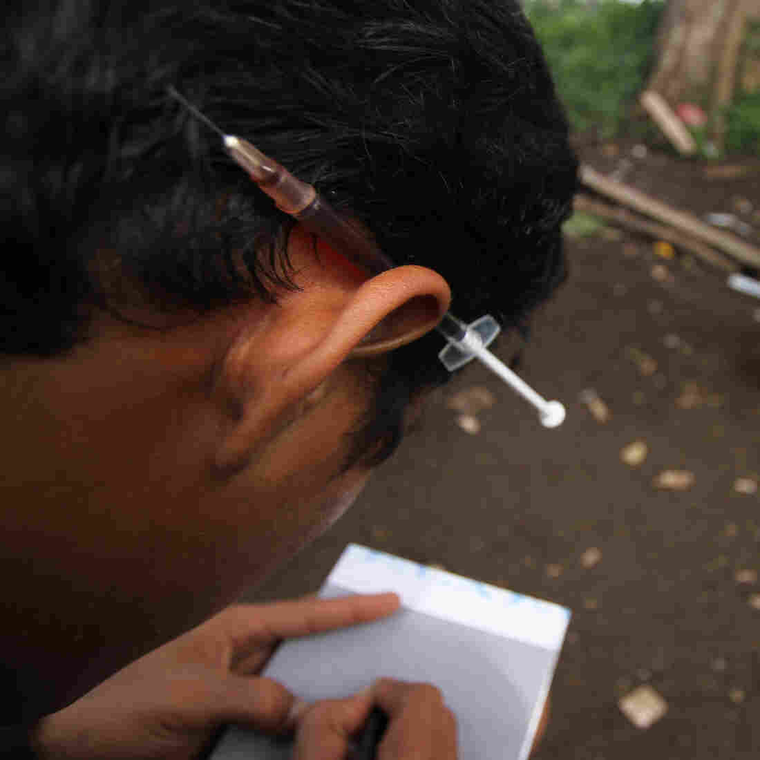 A heroin user keeps a syringe tucked behind his ear at a park in the city of Medan on Indonesia's Sumatra island. Cordita-Caritas Medan, a nongovernmental organization active there, works to reduce HIV infections through rehab of drug users and a needle exchange program.