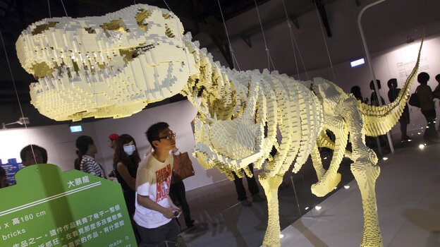 "A visitor looks at artist Nathan Sawaya's Lego sculpture ""T-Rax"" at ""The Art of the Brick"" exhibition in T"