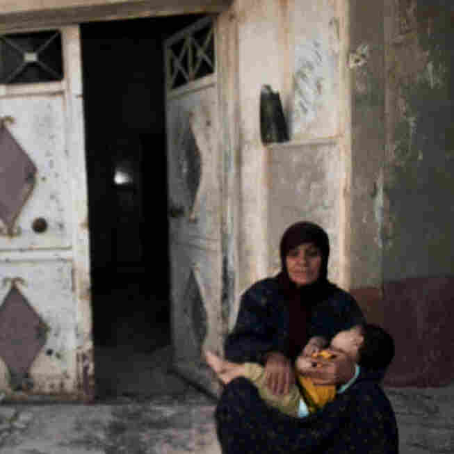 In this image provided by the Syrian opposition's Shaam News Network, a woman holds a child in front of their destroyed home in Tremseh, Syria, on July 14. The authenticity, content, location and date have not been independently verified.