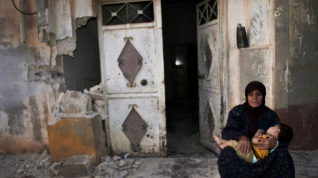 In this image provided by the Syrian opposition's Shaam News Network, a woman holds a child in front of their destroyed home in Tremseh, Syria, on July 14. The authenticity, content, location and date have not been independently verified. (AP)