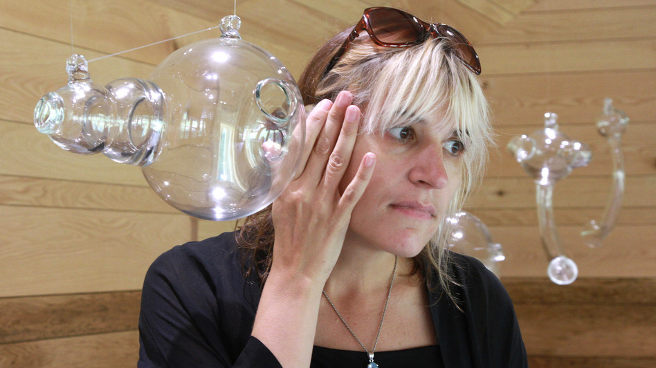 Artist Andrea Polli listens to modified bat sounds through a glass vessel inspired by Helmholtz resonators at the Marsh-Billings-Rockefeller National Historic Park in Woodstock, Vt. (Herb Swanson for NPR)