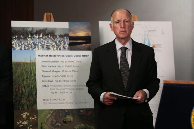 Gov. Jerry Brown waits for the start of a news conference to announce plans to build a giant twin tunnel system to move water from the Sacramento-San Joaquin River Delta to farmland and cities.