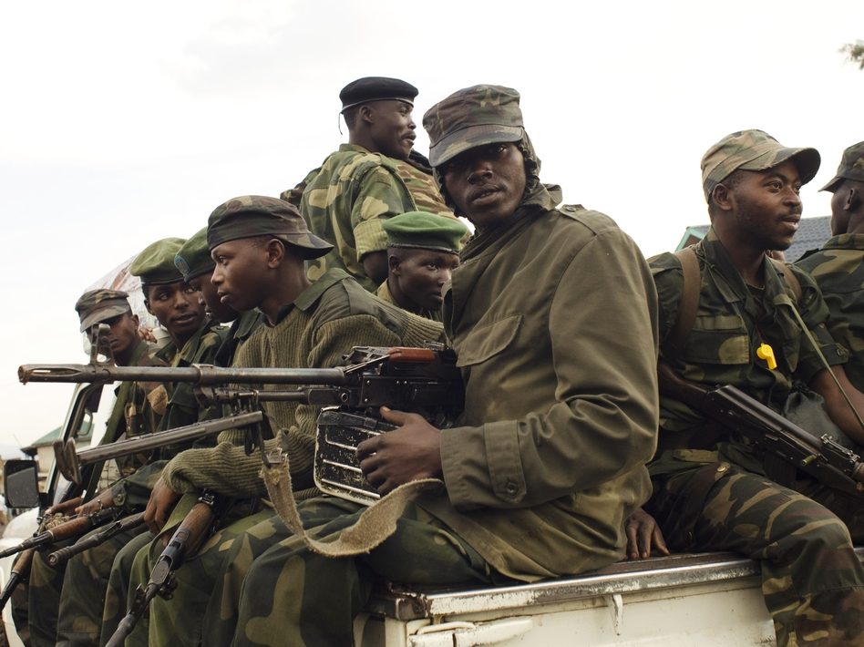 M23 rebels sit at the back of a pick-up truck captured a week before and formerly used by the Armed Forces of the Democratic Republic of Congo as they carry supplies through Bunagana on July 15.