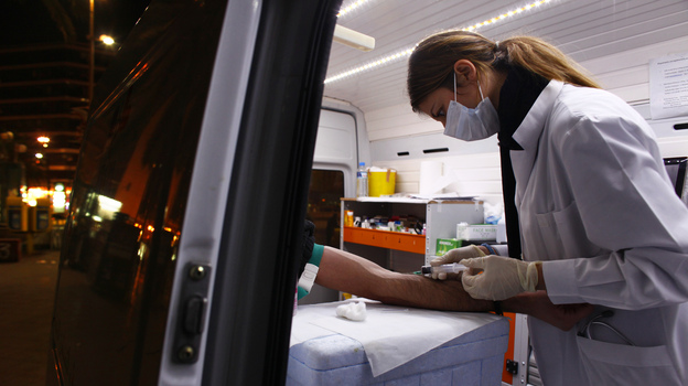 Nurse Maria Vatista draws blood from a Greek drug addict for an HIV test in a mobile testing van in Athens last year. HIV infection rates are rising, as Greece's financial crisis has led the government to cut health and social services, including a successful needle exchange program. (Reuters/Landov)